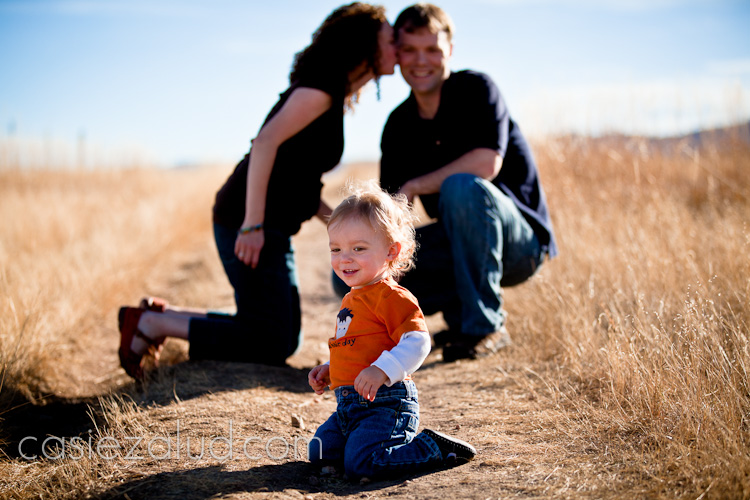 family portraits: one year old son in the front and parents in the background kissing