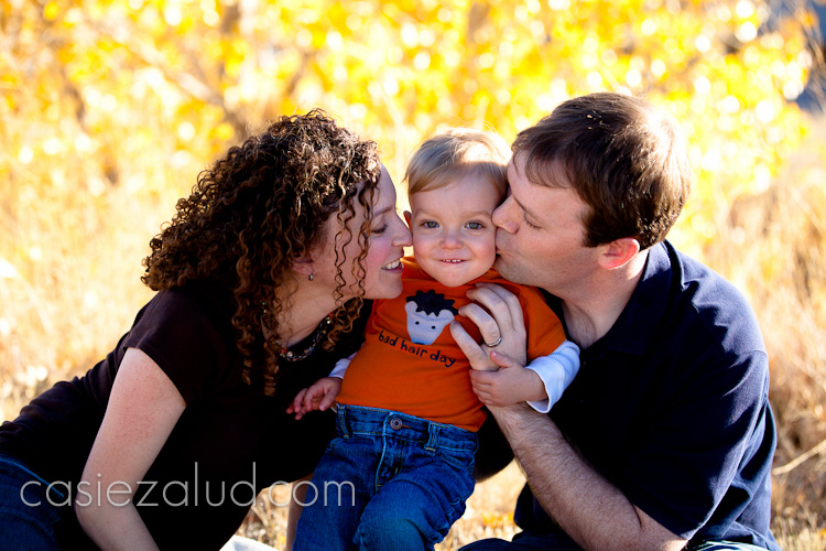 family portraits: mom and dad kissing one year old son on each of his cheeks infront of a golden aspen tree
