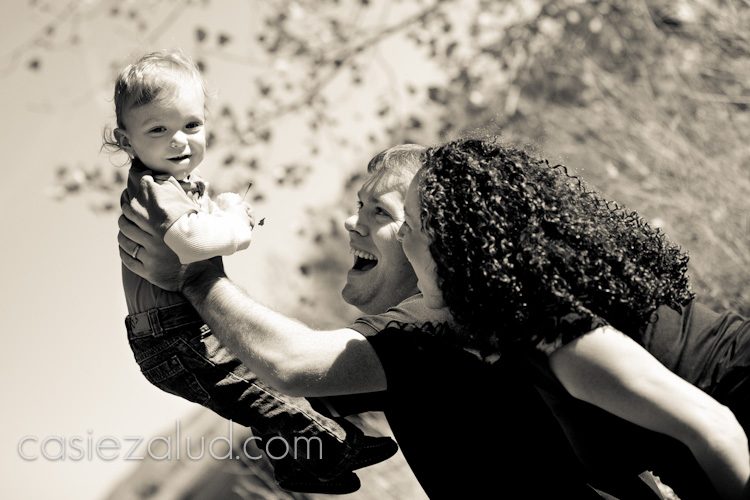 family portraits: dad holding one year old son up over his head as he smiles