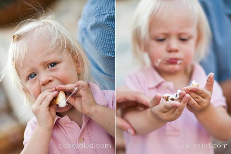 small girl trying to eat marshmellows