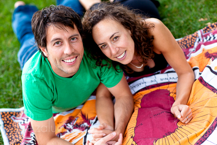 enaged couple in the park on a blanket looking up at the camera