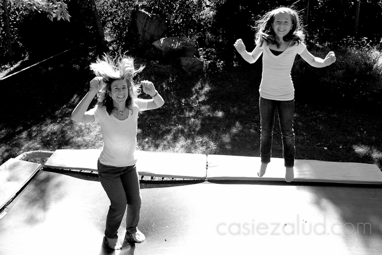 mom and daughter jumping on a trampoline