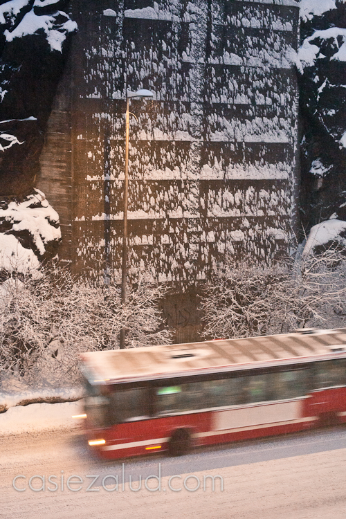 image out a window of a snow storm against rocks and a bus passing under the light