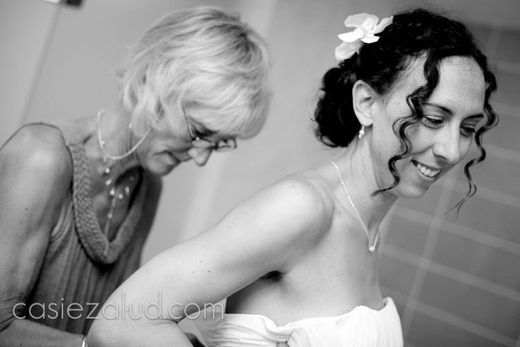 mom zipping bride into dress