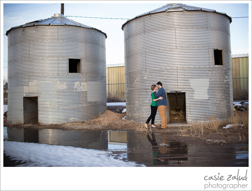 Engagement couple kissing infront of silos in the winter