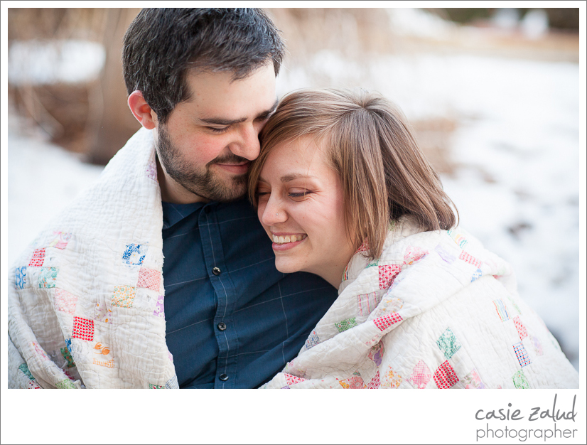 Intimate moment of engaged couple snuggling under a quilt outside
