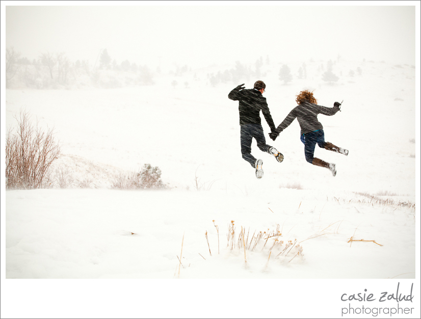 engaged couple jumping in a snowstorm in Boulder