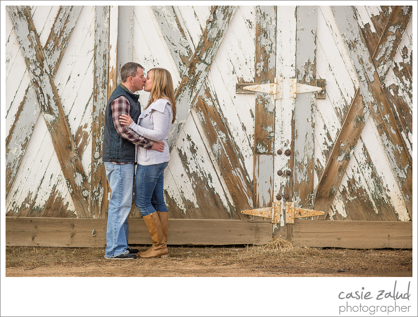 Engaged couple kissing infront of old barn in Nederland, CO.