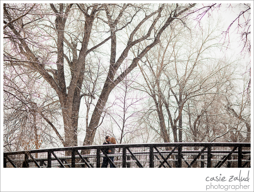 Engaged couple kissing on bridge over Boulder Creek in the snow