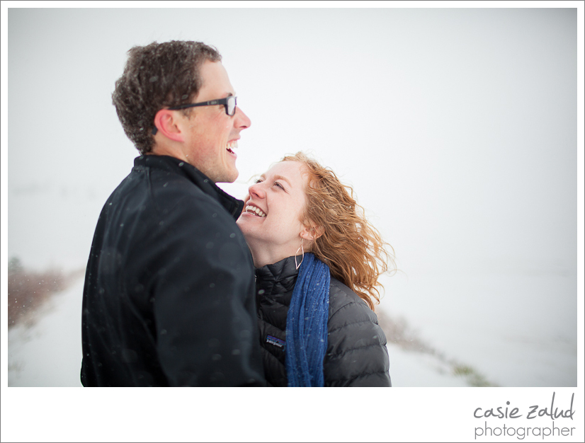 engaged couple laughing in snowstorm at Daddy Draw trail in Boulder