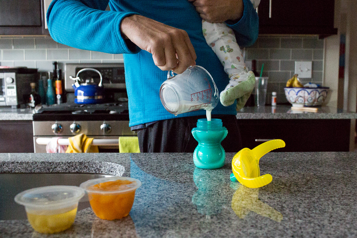 adult holding a kid and pouring milk into a turquoise cup