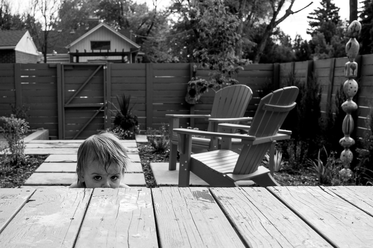 a toddler sitting on a step of a deck peering at the camera but hiding a bit on step and only seeing the top of her head