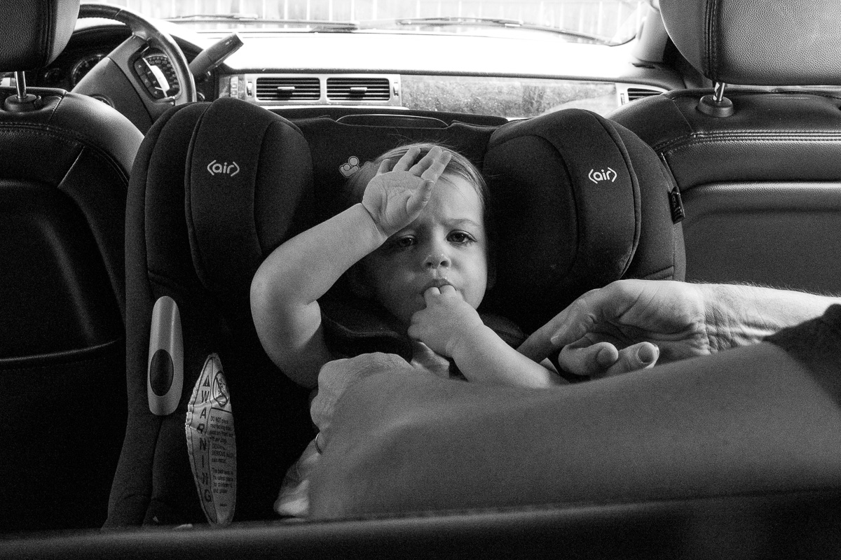 Toddler in car seat facing backwards with one hand on her forehead as she chews on her fingers looking very tired