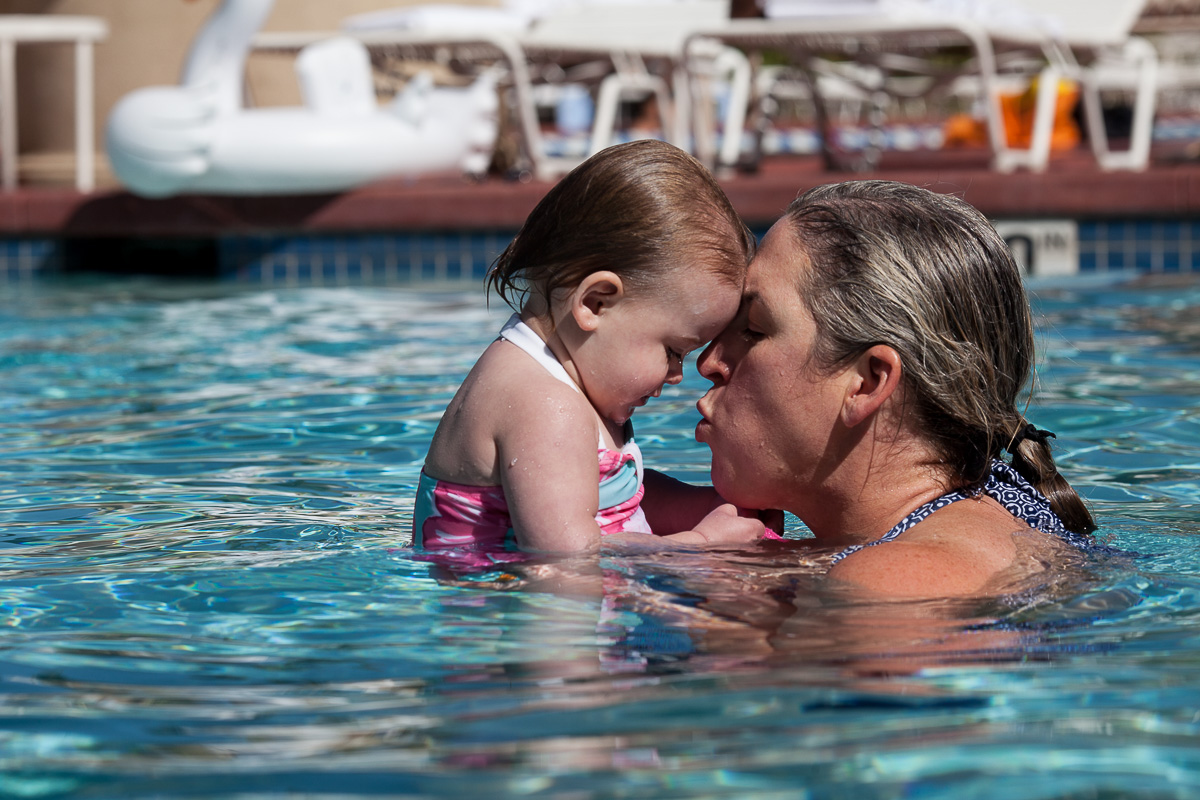 mom holding a toddler and kissing her in a pool