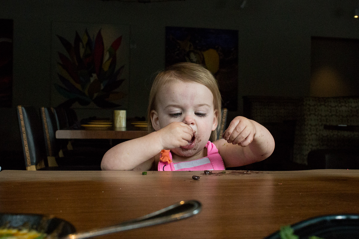 Toddler in hot pink tank top shoving food in her mouth in at high chair at the table