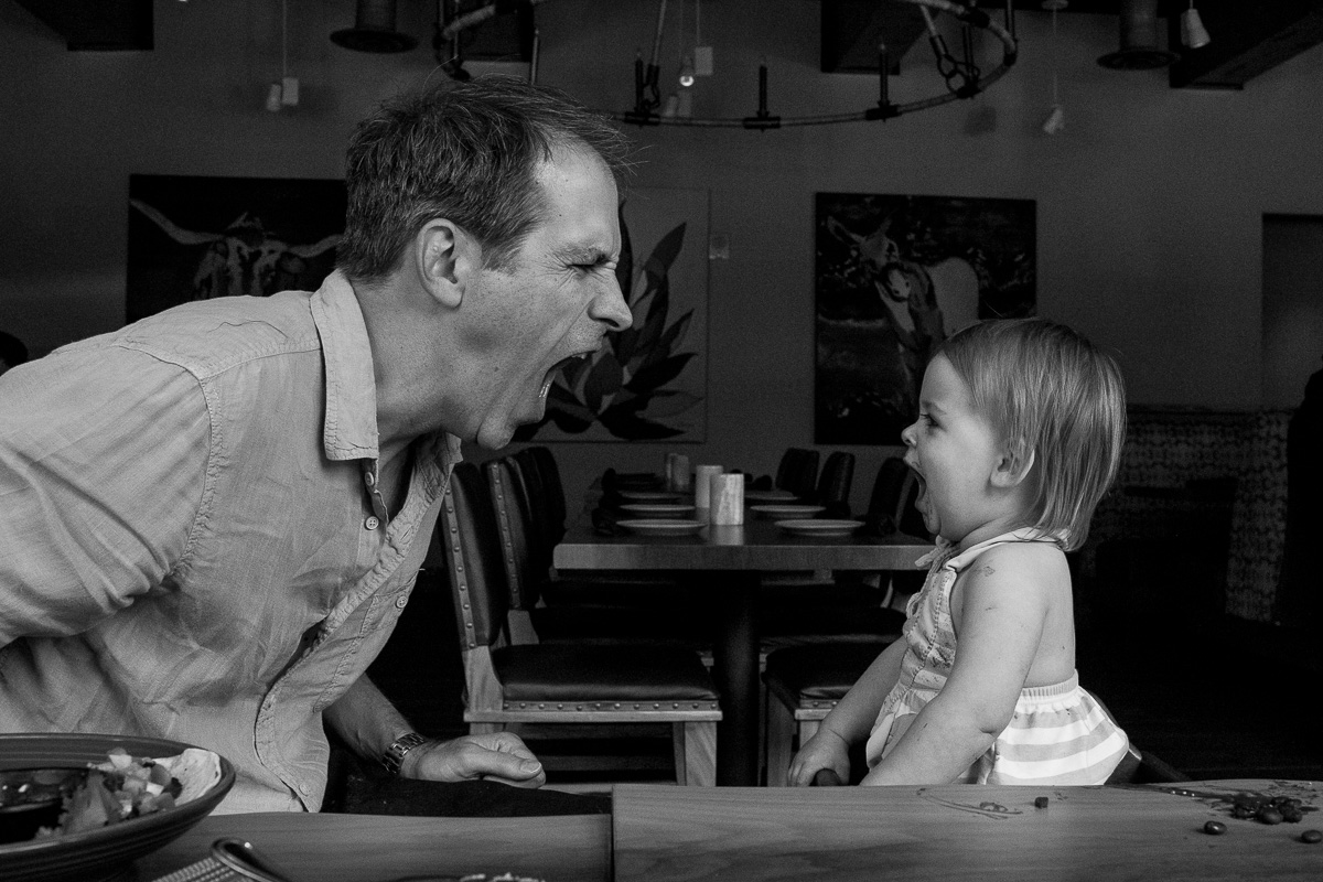 black and white image, dad and toddler facing each other screaming