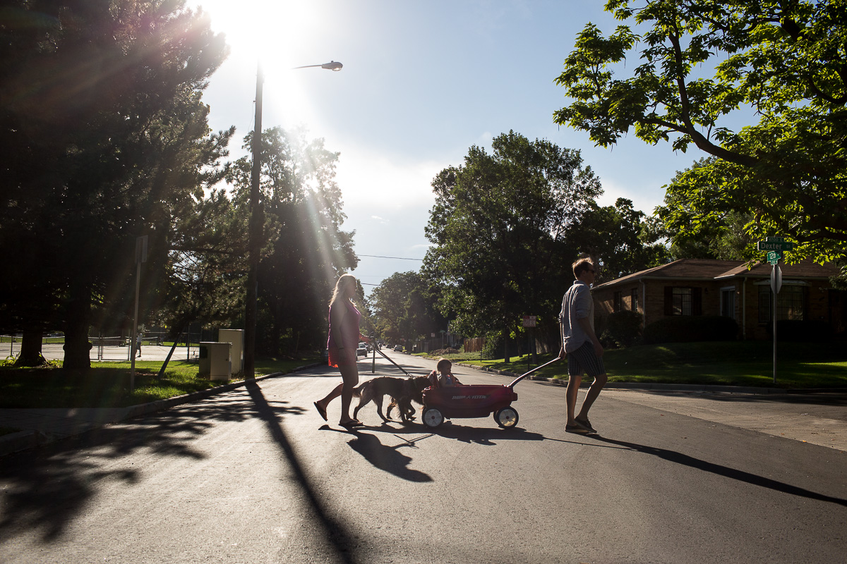 backlit image with sun in the top left corner, dad pulling wagon with toddler in it and mom walking behind with two dogs