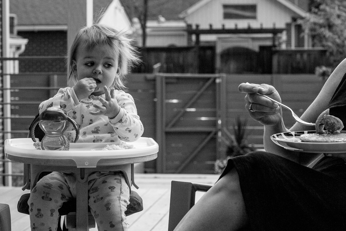 black and white photo of a child eating and looking longingly at mom's plate of food as she takes a bite