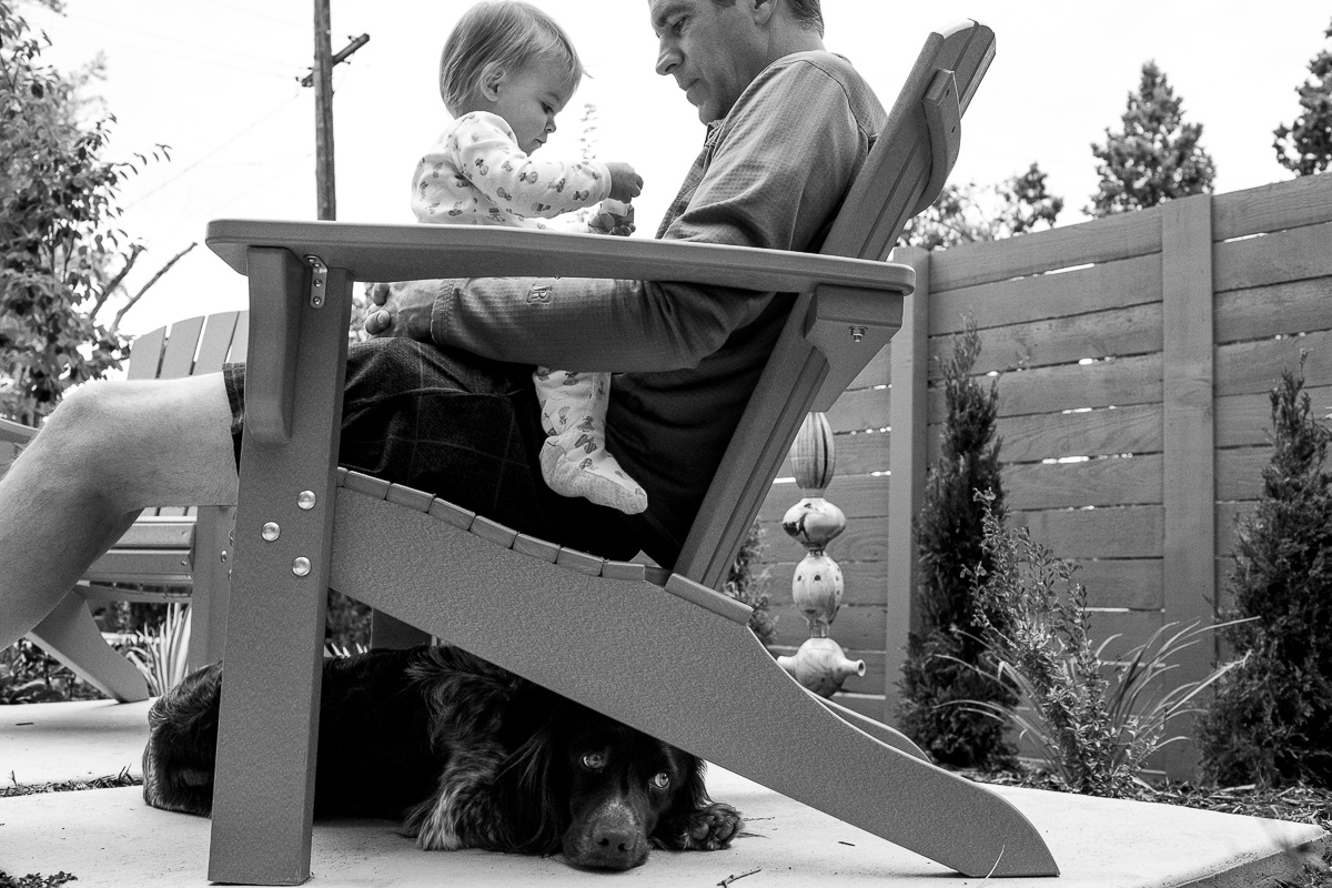 black and white photos of a toddler sitting on dad's lap while the family dog sits under their chair