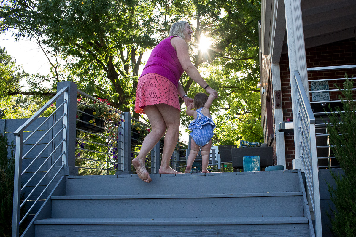 Mom in pink shirt and orange skirt holding her toddler hands above the toddler's head as she helps her toddler walk up the stairs of their deck outside