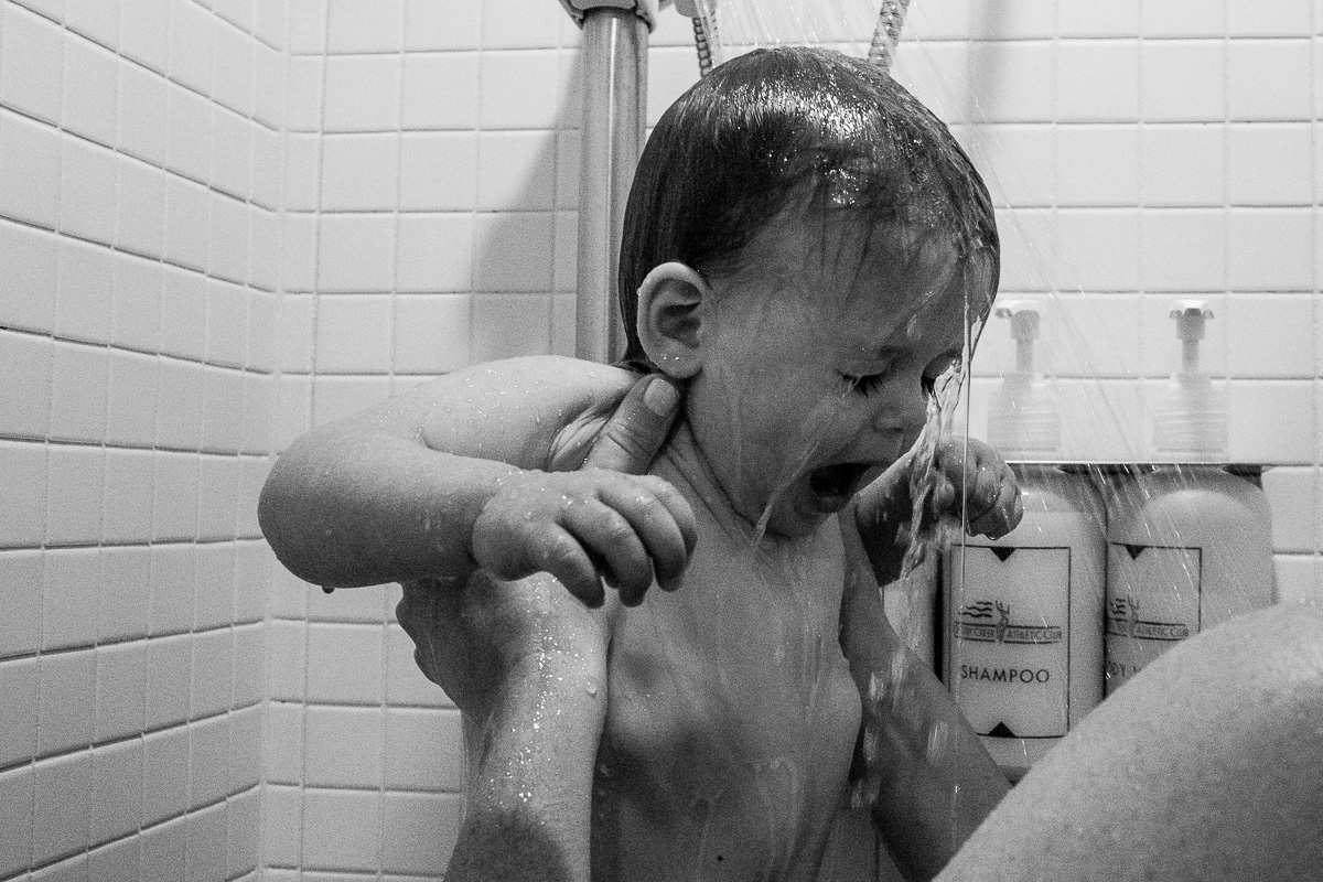 black and white images of an adult holding a toddler up under a shower head as she gasps for a breath