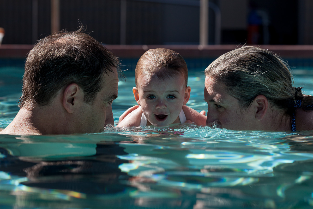 Family of three in a pool, parents in water up to their noses like they are blowing bubbles with toddler in the middle