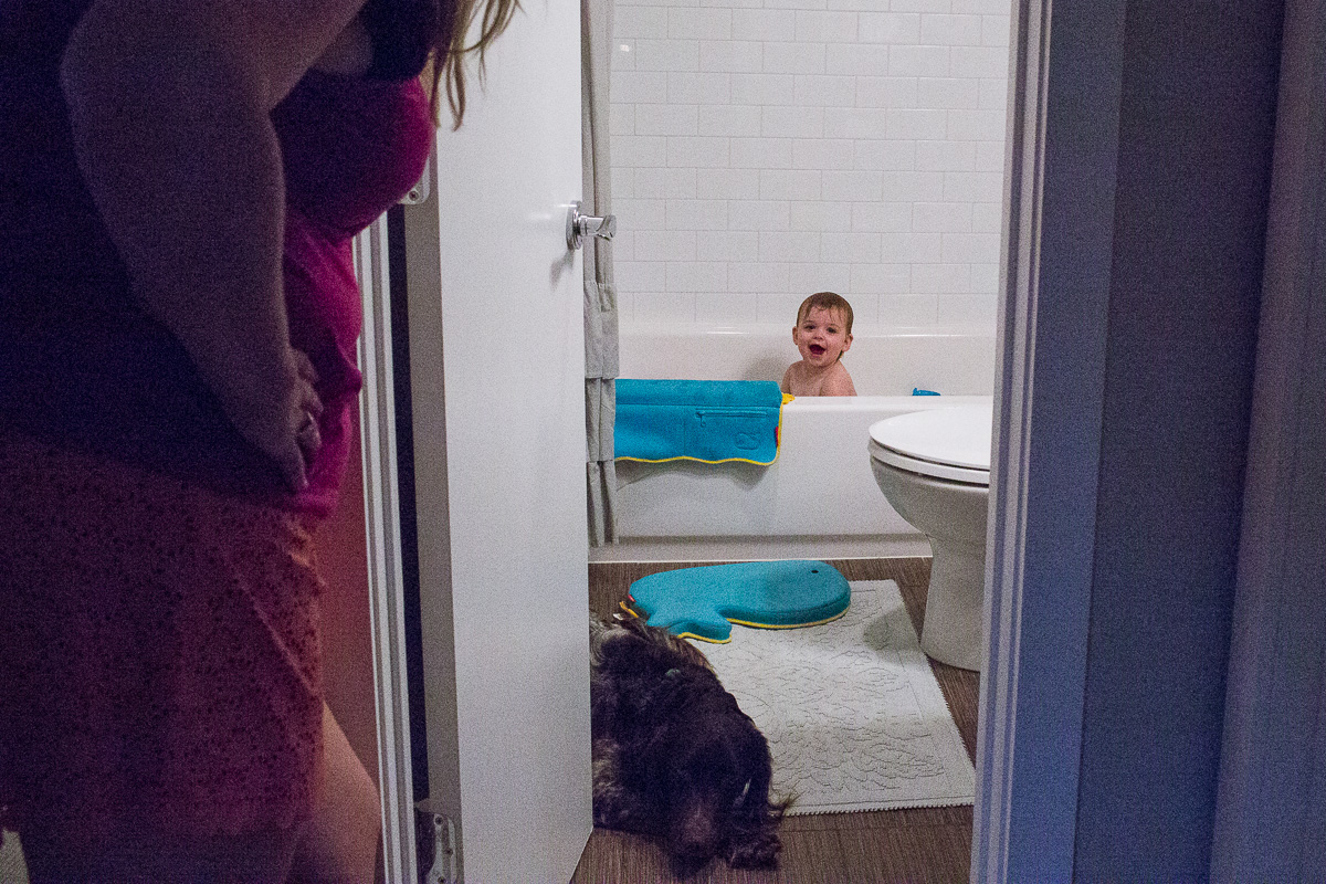 a mother peaking into the bathroom while her toddler is in the bath and the family dog lays on the bathroom floor
