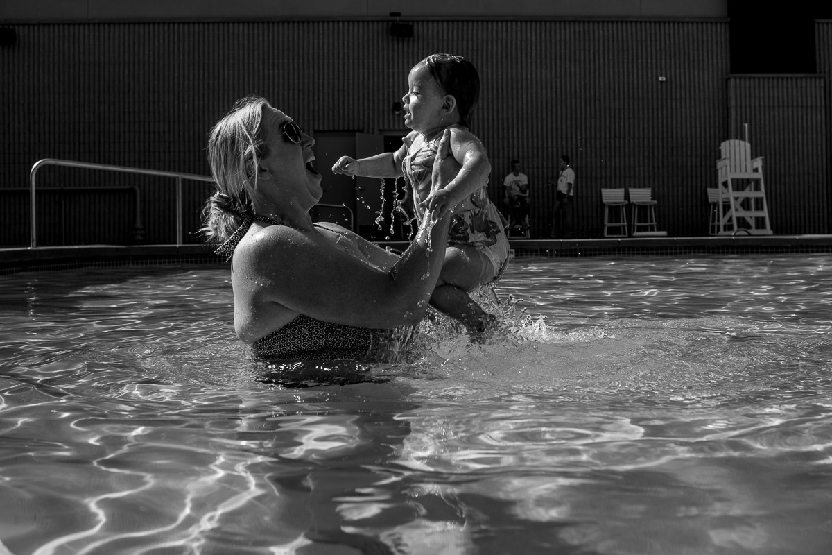 black and white picture in the pool of a mom jumping out of the water while holding her toddler as toddler was joyous with smile