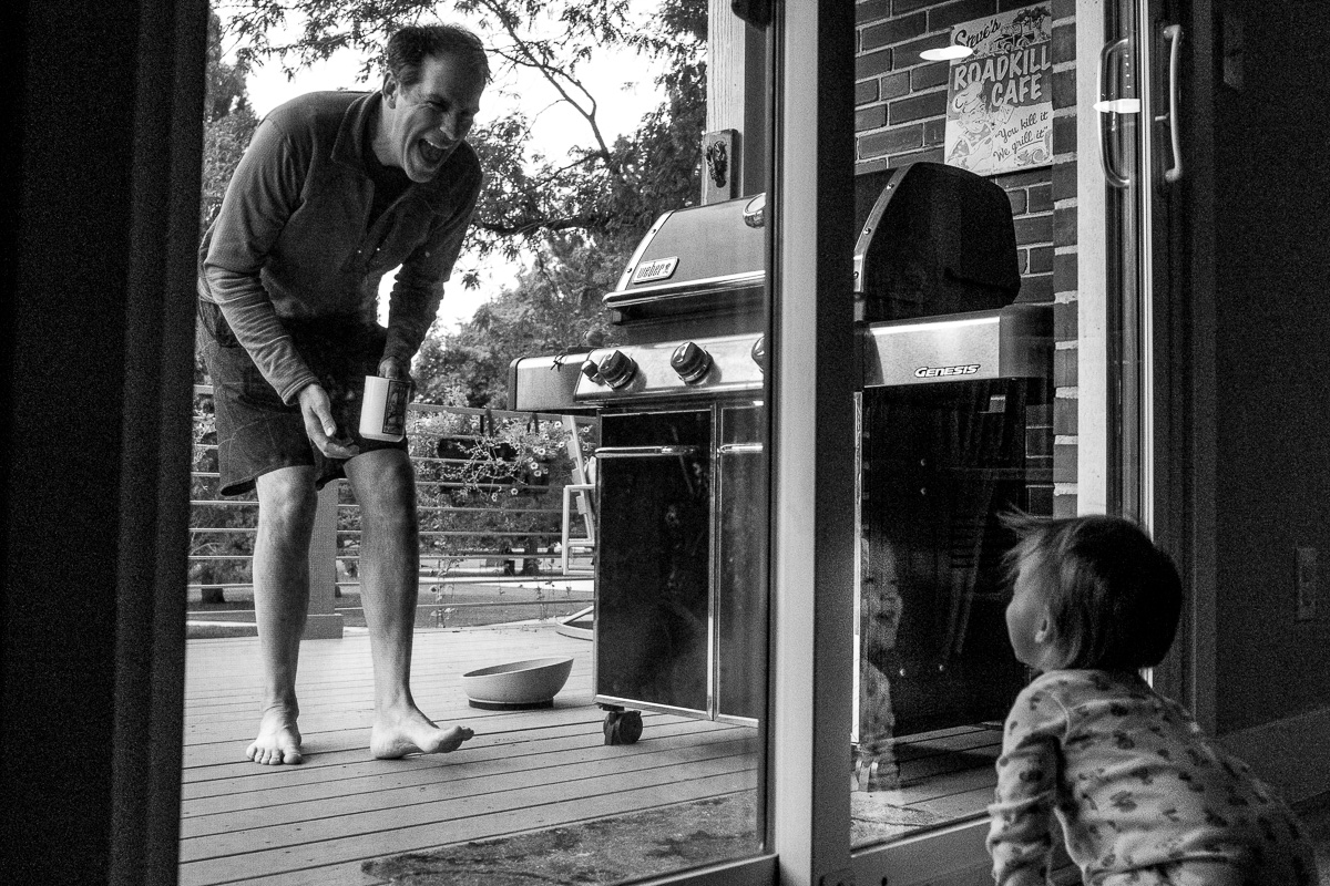 dad outside the sliding glass door making a silly face at the crawling toddler who is laughing hysterically