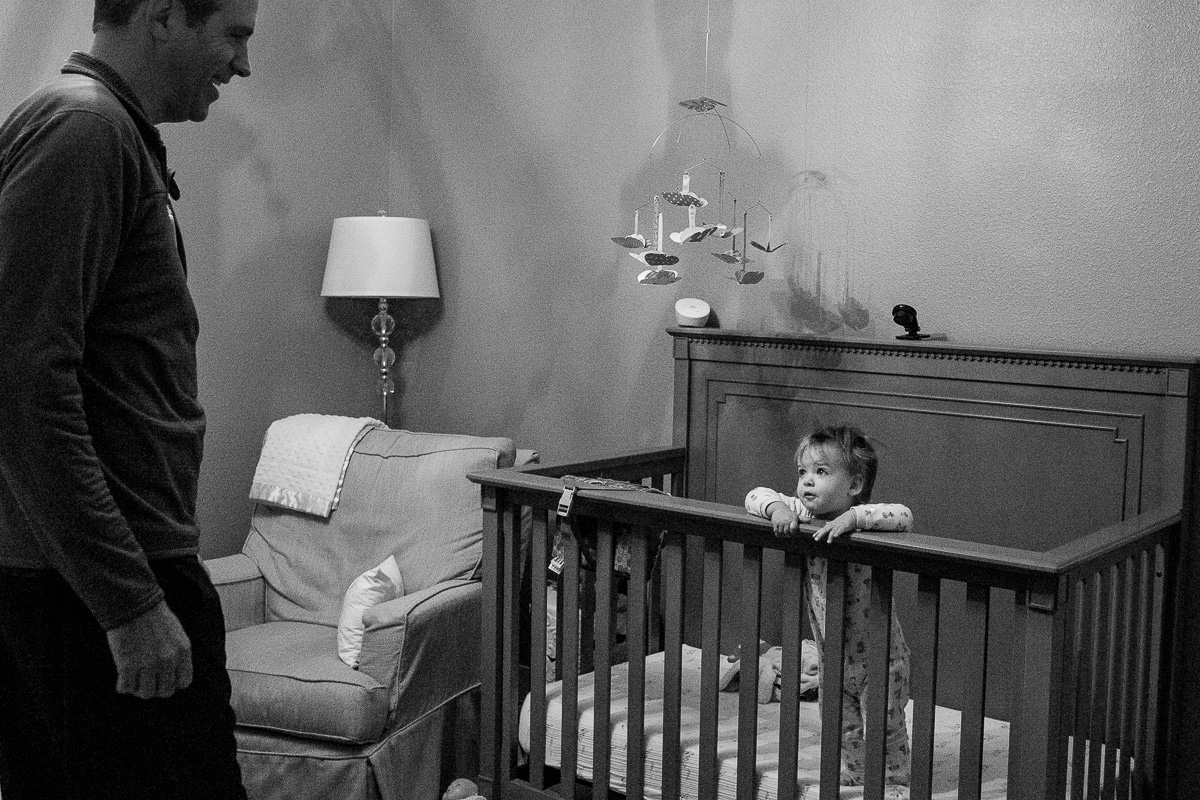 black white photo of a toddler hanging on the side of her crib looking up at dad wanting him to pick her up