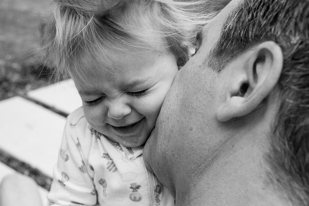 black and white close up of dad kissing his toddler and her loving it