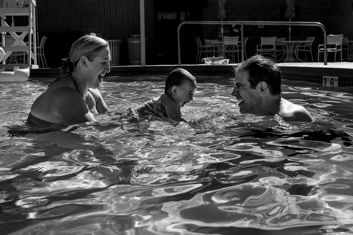 black and white picture of mom passing a toddler to dad in a pool while everyone is smiling and laughing