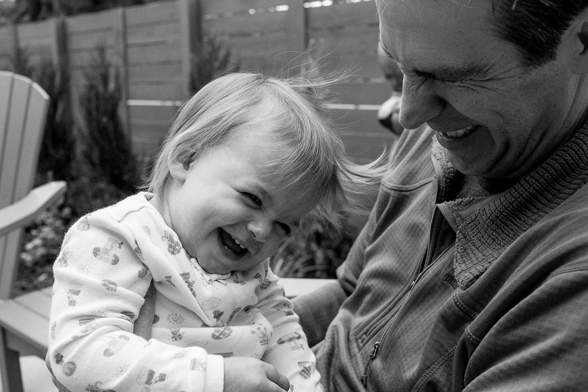 black and white close up of a toddler on her dad's lap as they both are giggling like crazy