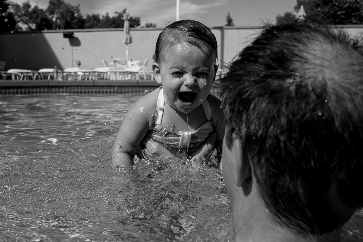 black and white picture from behind dad's shoulder looking at a toddler giggling in the water