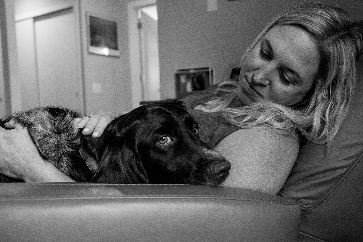 black and white close up of dog in woman's lap snuggling into her arm pit