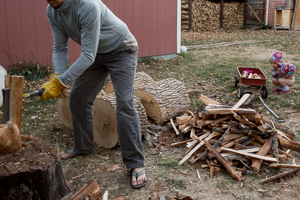 man chopping wood in flip flops child peeing in background