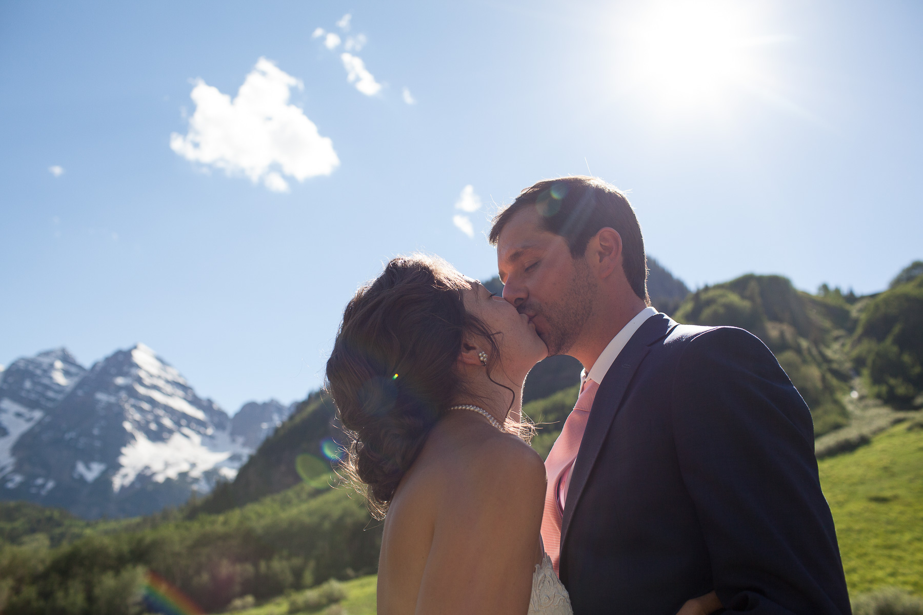 a bride and groom kissing each other with the Maroon Bells in the background
