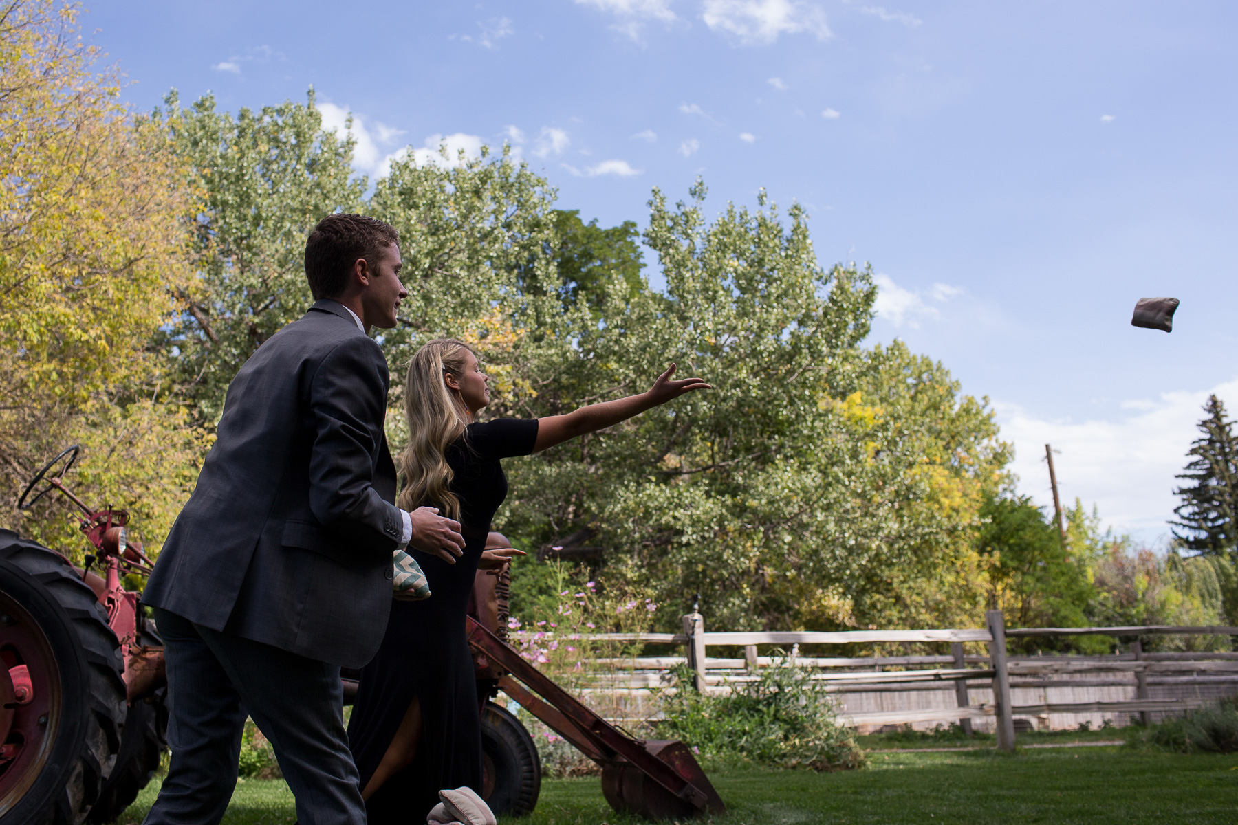 A female wedding guest tossing a corn hold bean bag on a farm with a male guest