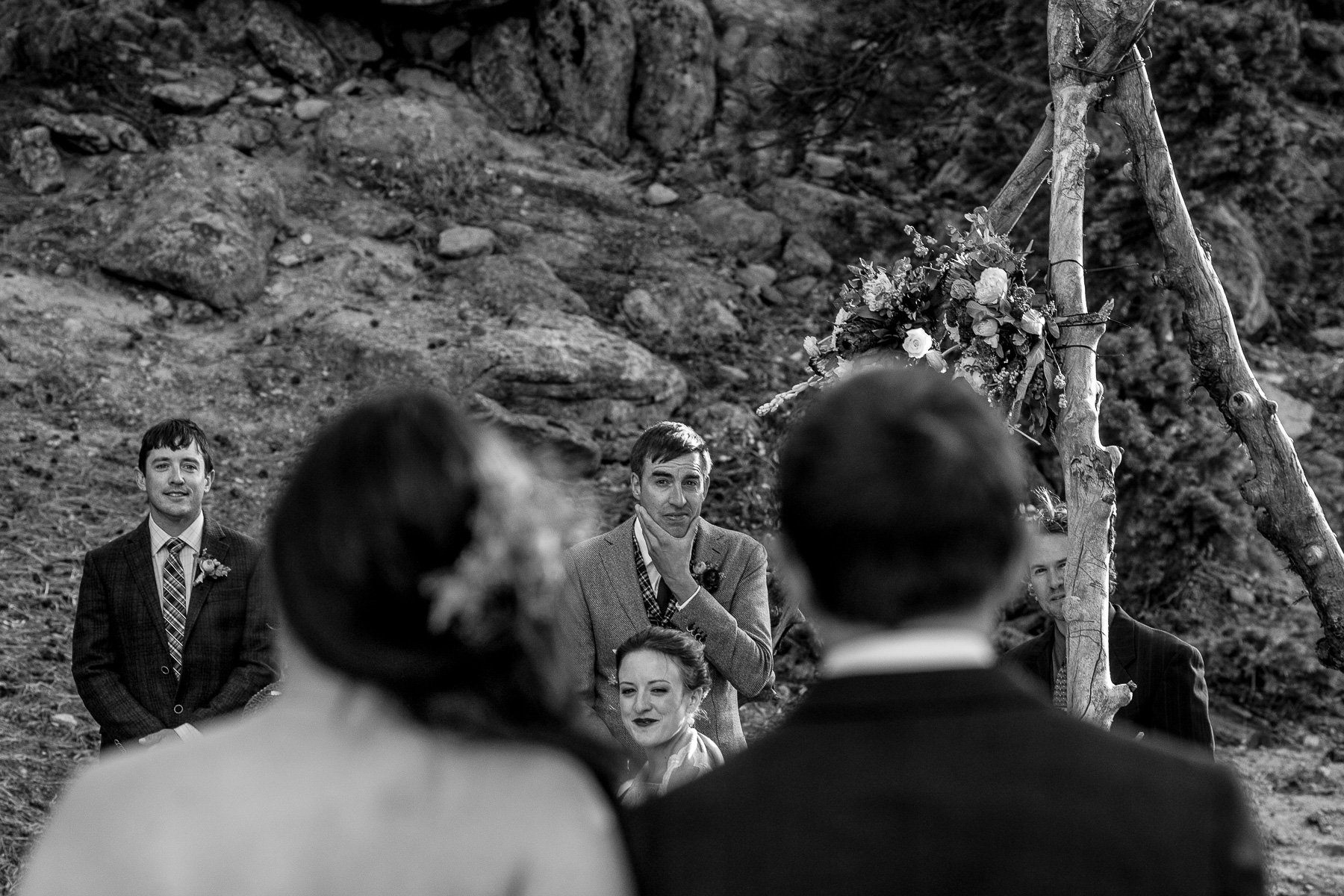 Looking through the shoulders of a bride and her father as she approaches her groom at the alter