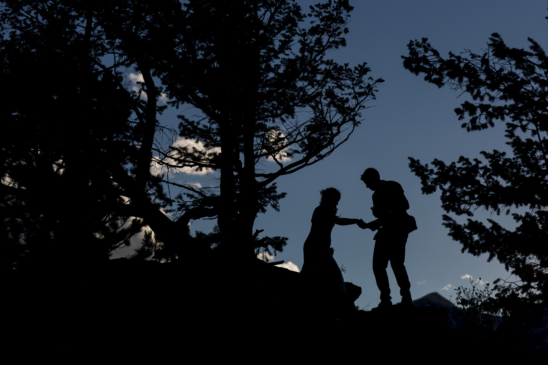 a silhouette of a bride and groom at sunset on walking on rocks