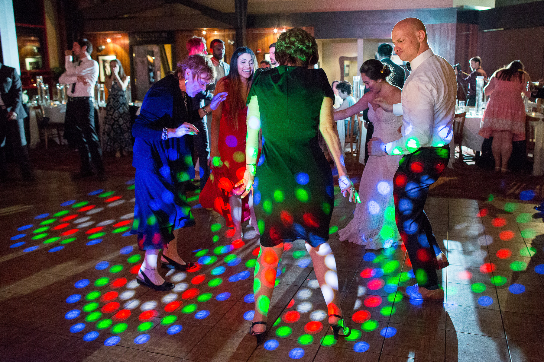 older women, a bride and a guy making a duck face dancing at an indoor wedding with crazy lights