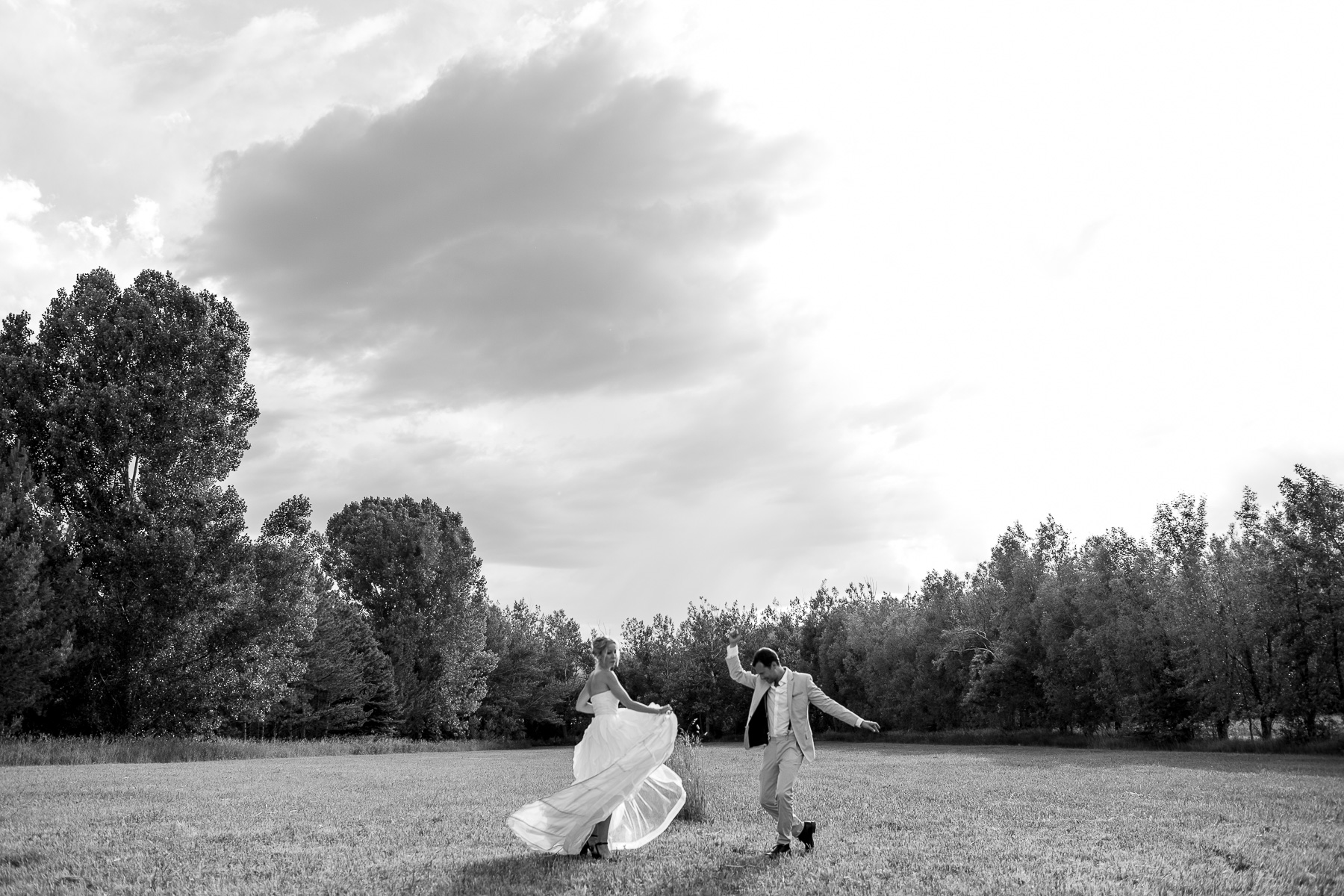 a bride and groom dancing side by side in a field