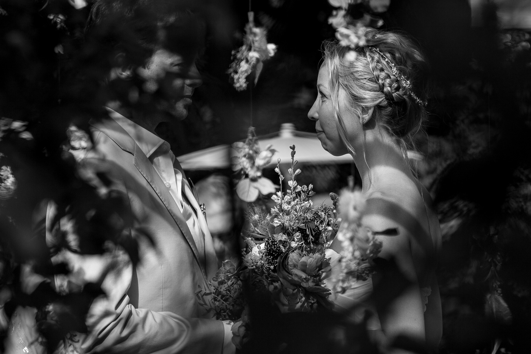 a bride during her wedding ceremony looking intensely at her husband with a tear on her cheek