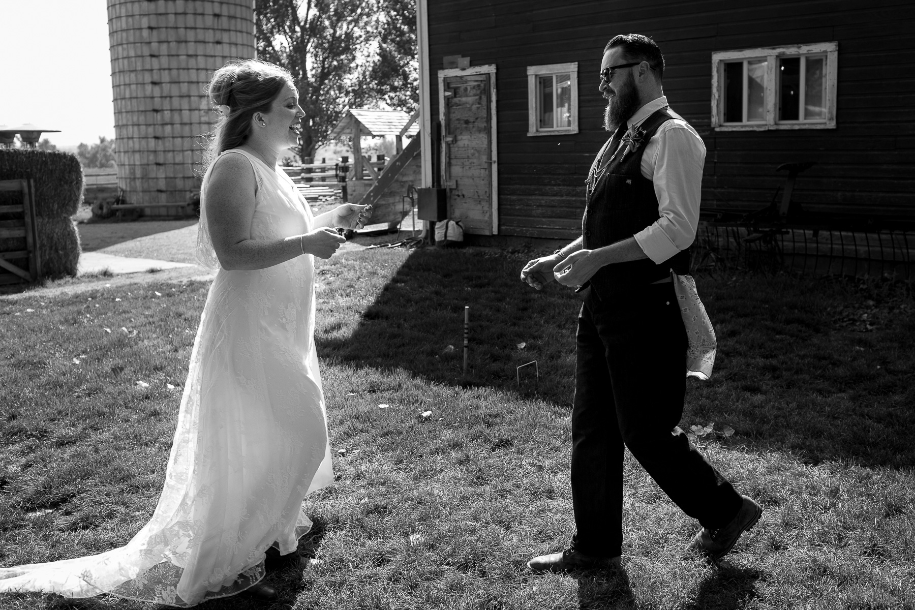 a backlit bride and groom walking towards each other on a farm