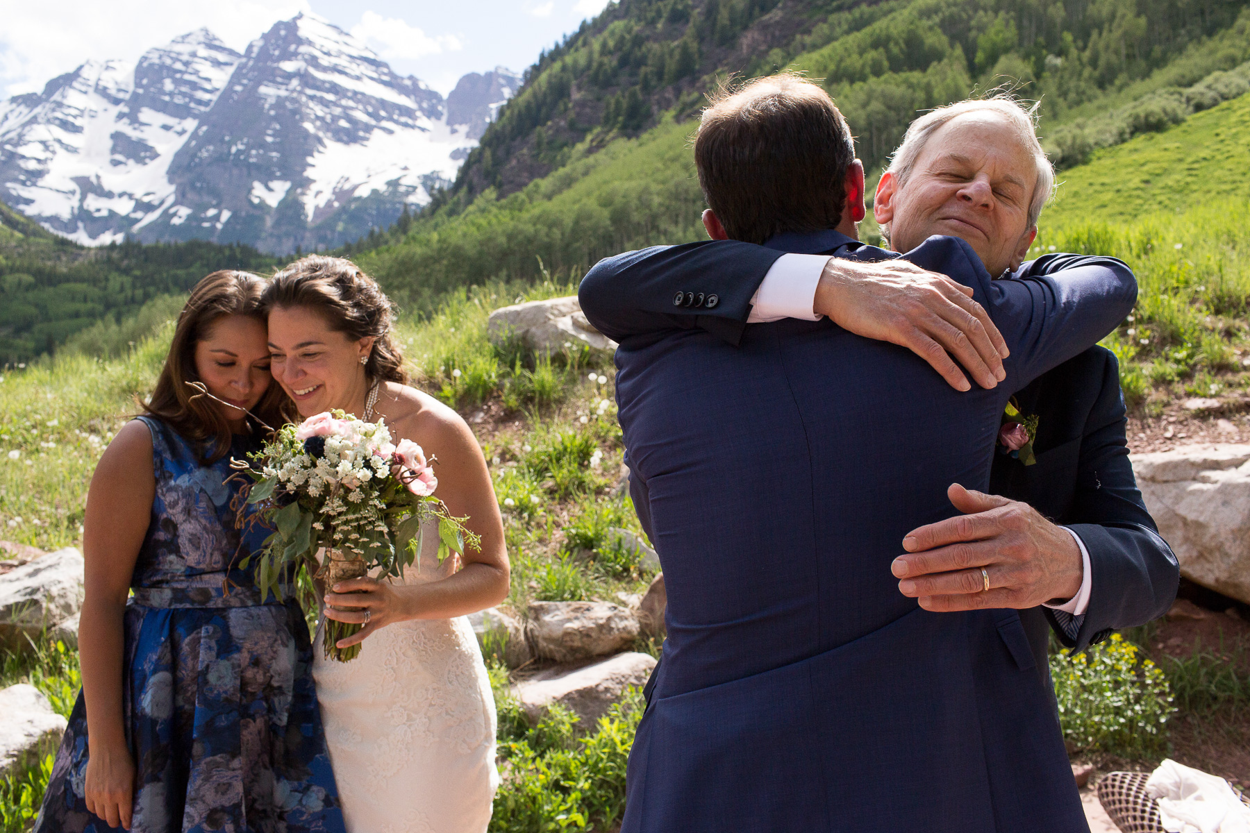 a groom hugging the father of the bride besides a bride who hugs the sister of the groom in front of the Maroon Bells