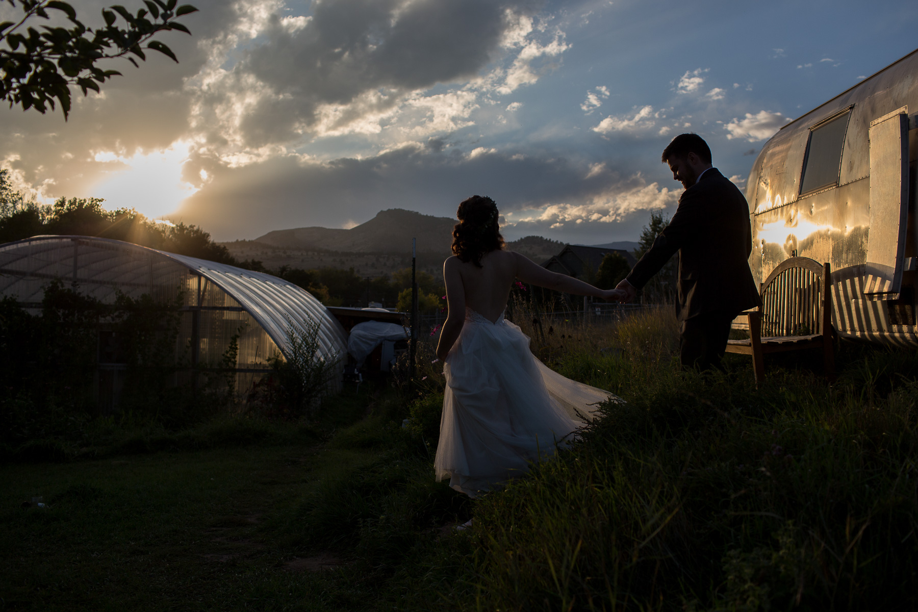 Bride leading groom down a step in the grass at sunset beside an airstream