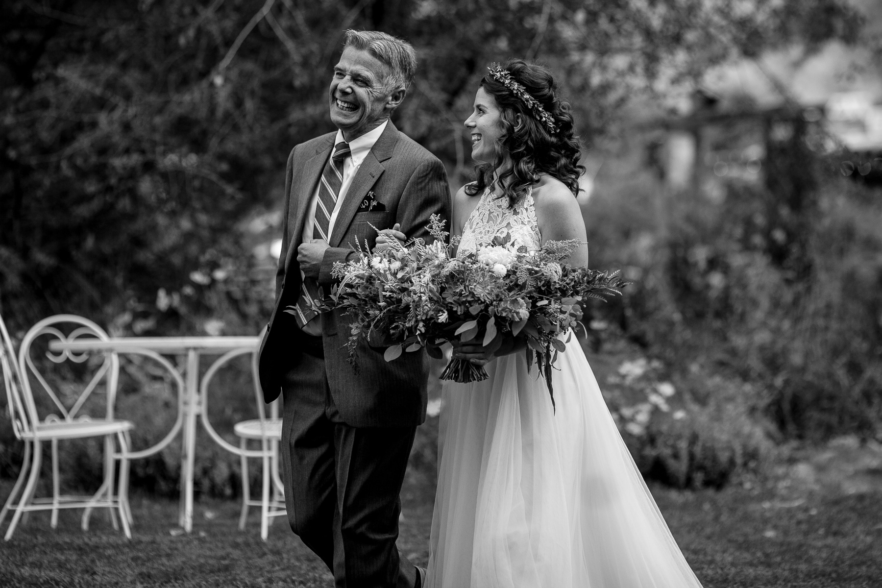 A bride and her dad walking down the aisle at an outdoor farm wedding