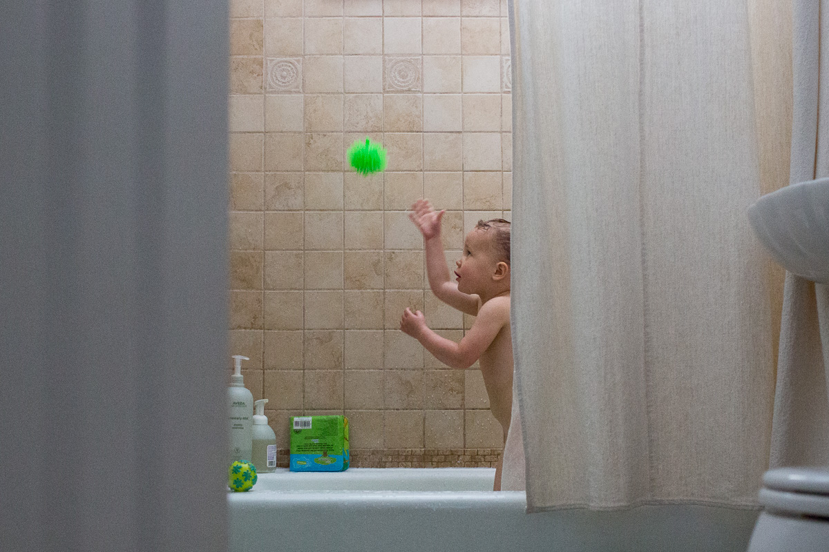 Toddler barely peaking from behind the shower curtain in the bath tub throwing a green ball in the hair