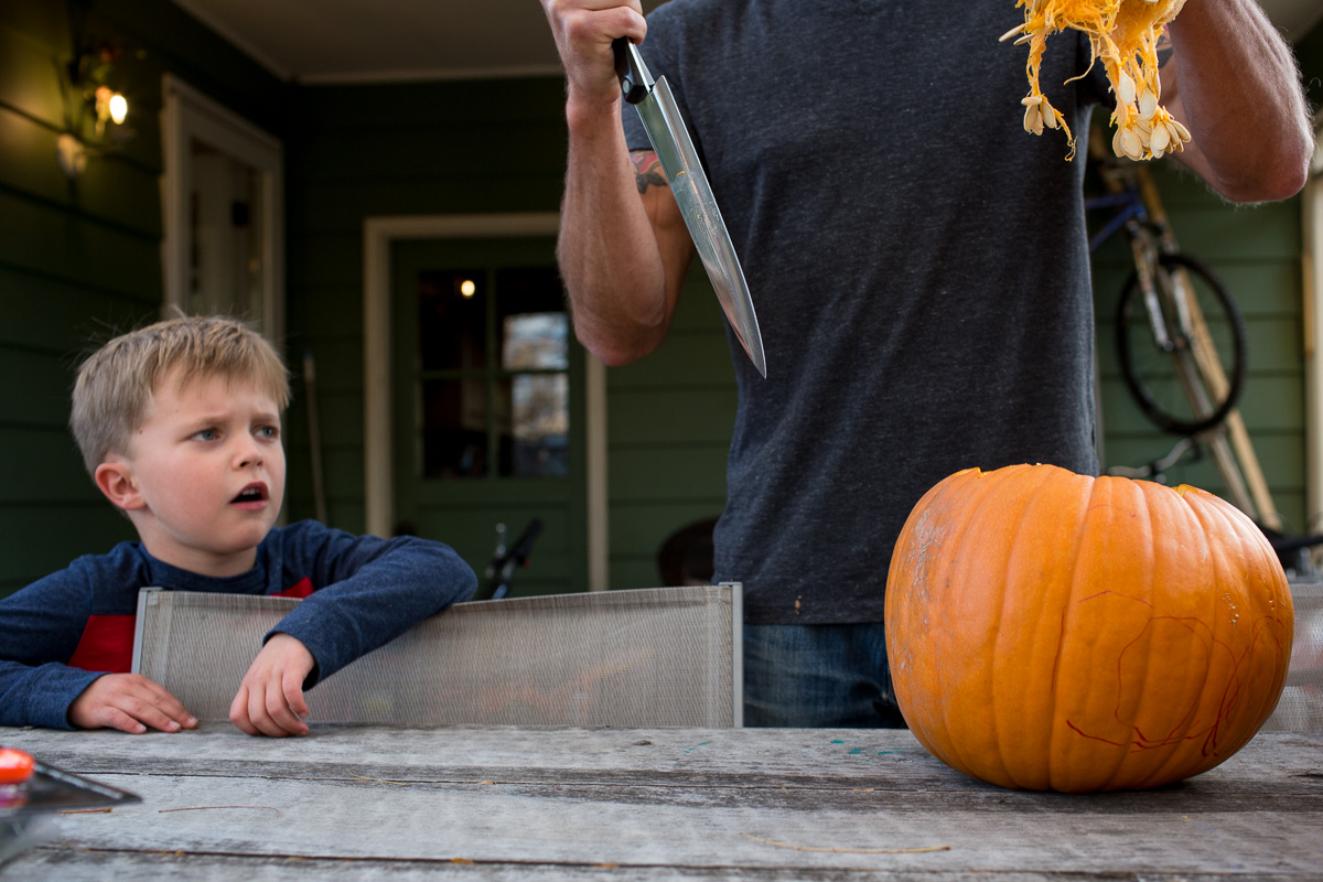 a pumpkin with top cut off and inside hanging down, knife in man's hand and a toddler reacting to it