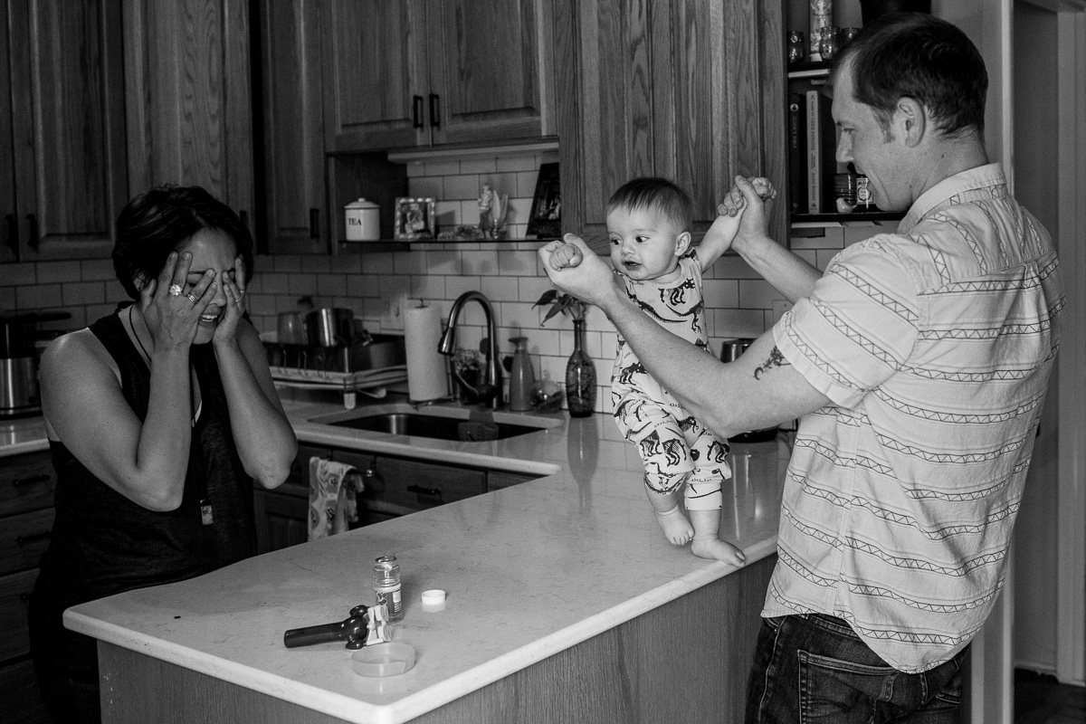 Mom with hands over her face as her toddler dances on the counter with the help of dad